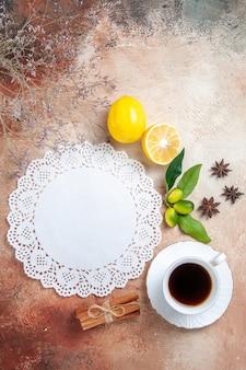 Vista vertical de una taza de té, té negro, servilleta de limón y té en coloridos