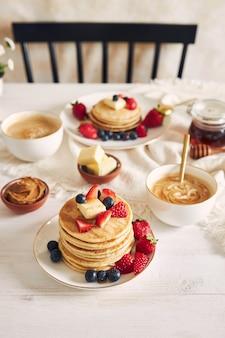 Vista vertical de tortitas veganas y frutas coloridas en el desayuno