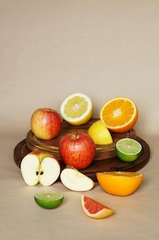 Vista vertical de varias verduras y frutas en un objeto de madera circular