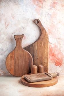 Vista vertical de varios tipos de tablas de cortar de madera de pie sobre una superficie colorida