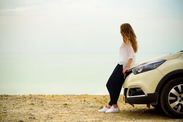 Vista del viajero de la mujer joven que mira la puesta del sol del mar, sentado en el auto hatchback