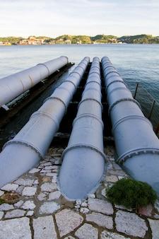Vista de los viejos tubos de aguas residuales que llevan a un río.