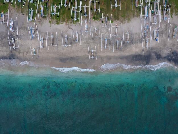 Vistas aéreas del mar y la playa con barcos tradicionales de madera.
