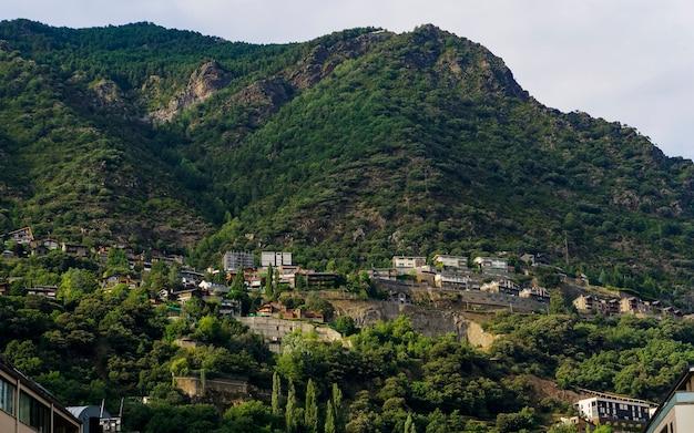 Vistas de edificios en una montaña verde con un cielo sombrío