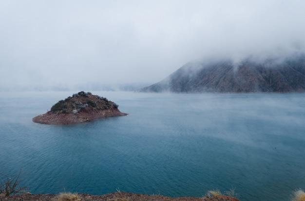 Vistas a una pequeña isla con una montaña cubierta de nieblas durante el invierno