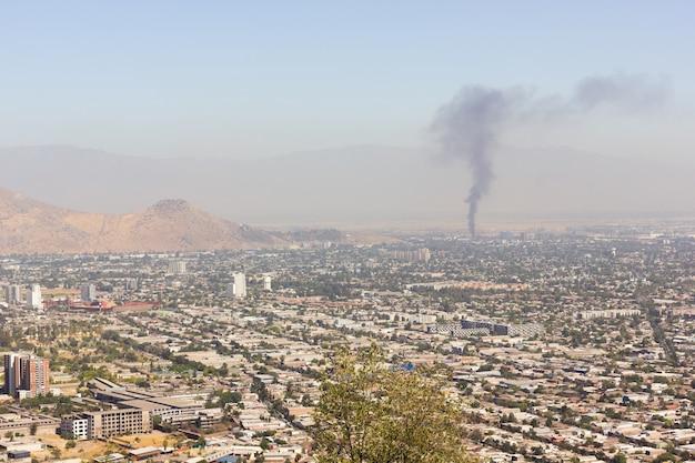 Vistas planas de la ciudad de santiago con humo de fuego en el fondo día soleado en la capital contaminada de chile