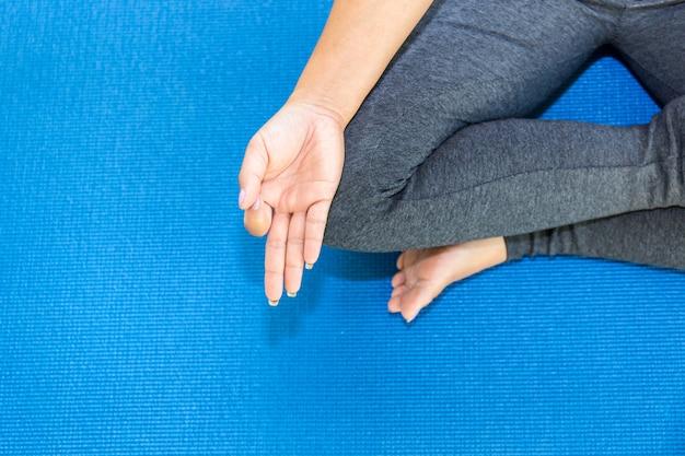 Vistas superiores atractiva joven trabajando en casa, haciendo ejercicio de yoga en la alfombra azul