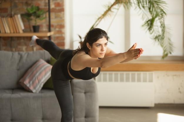 Vitalidad. deportiva árabe, musulmana hermosa joven tomando lecciones profesionales de yoga en línea y practicando en casa. concepto de estilo de vida saludable, bienestar, bienestar, afición. flexible y motivado.