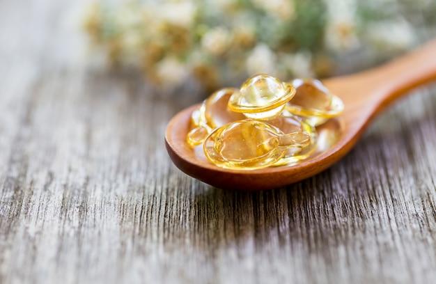 Vitaminas saludables en una cuchara de madera.