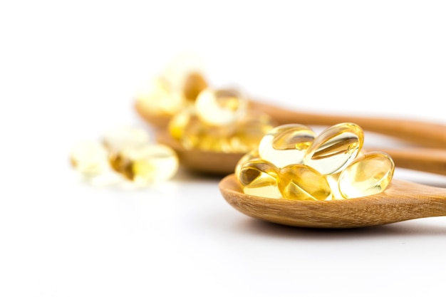Vitaminas sanas en una cuchara de madera con el fondo blanco.
