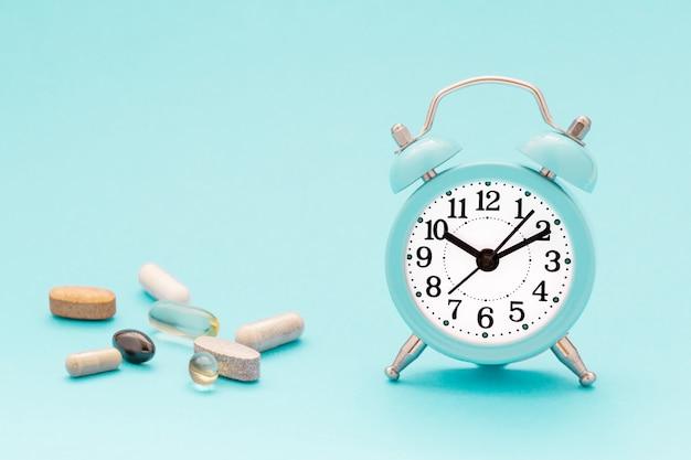 Vitaminas, suplementos y despertador sobre fondo azul pastel.