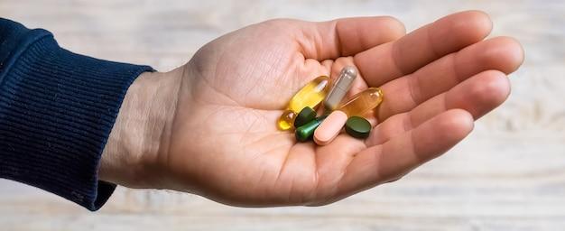 Vitaminas y suplementos dietéticos en una mano. enfoque selectivo. personas.