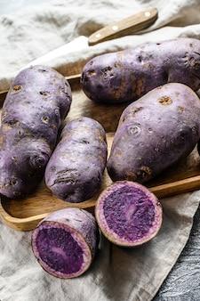 Vitelotte patata cruda en una tabla de cortar.