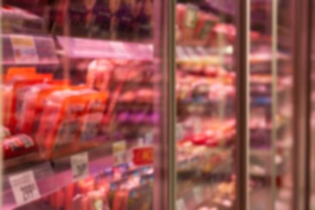 Vitrina de cristal con productos cárnicos refrigerados en la tienda. borroso. vista lateral.
