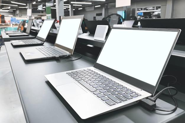 Vitrina de mesa con laptops en la tienda de tecnología. elegir y comprar una computadora portátil en una tienda de tecnología.