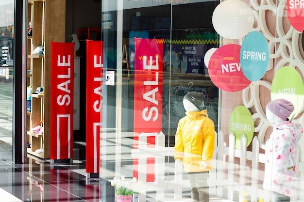 Vitrinas de una tienda de ropa con stands rojos con carteles de venta. tiempo de descuentos.