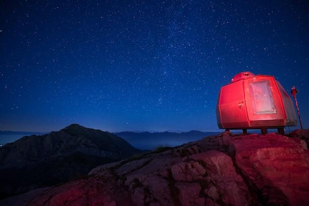 Vivac iluminado en rojo en las altas montañas bajo un hermoso cielo estrellado