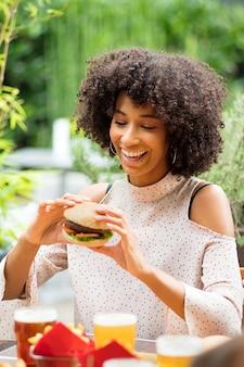 Vivaz feliz joven negra comiendo una hamburguesa sosteniéndola en sus manos con una sonrisa radiante y mirada de anticipación en un restaurante al aire libre
