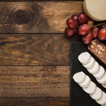 Vivid queso y uvas rojas sobre superficie de madera sucia