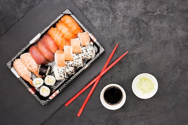 Vívidos rollos de pescado asiático en bandeja y palillos con salsa de soja y wasabi sobre piso de concreto