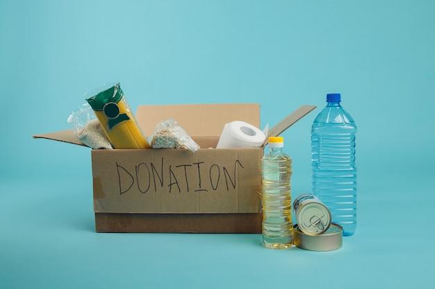 Vivienda de apoyo o donación de alimentos para los pobres. caja de donación sobre fondo azul.