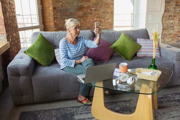 Vlog, blog, selfie. mujer mayor estudiando en casa, obteniendo cursos en línea, autodesarrollo. mujer caucásica que usa dispositivos modernos para divertirse, educarse, dedicar tiempo a un nuevo trabajo o pasatiempo.