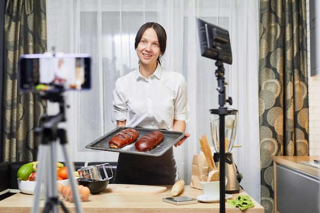 Vlog culinario. blog de repostería. mujer caucásica cocinar y hornear en las redes sociales. grabación de video en la cocina.