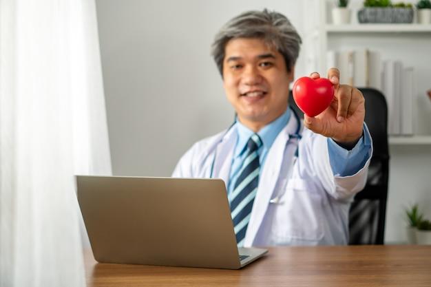 Vlog médico asiático blogger influencer grabando video blog para educar sobre enfermedades cardíacas al paciente