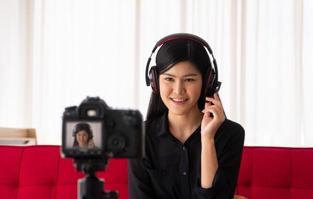 Vlog mujer influyente blogger asiática sentada en el sofá en casa y grabando video blog para enseñar y entrenar a sus estudiantes