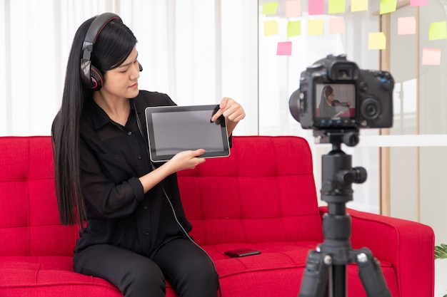 Vlog mujer influyente blogger asiática sentada en el sofá en casa y grabando video blog para enseñar a los estudiantes