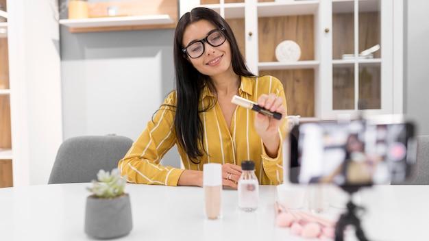 Vlogger femenina en casa con smartphone y productos de maquillaje