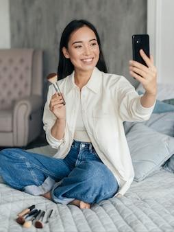 Vlogger femenina mostrando su pincel de maquillaje