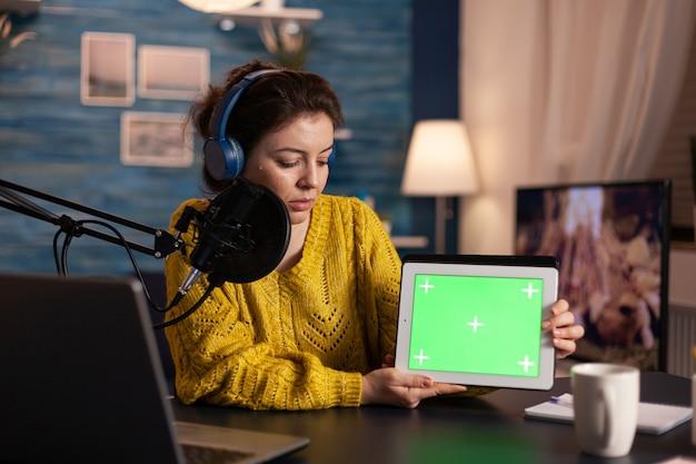 Vlogger mirando portátil y hablando de tableta con escritorio chroma key