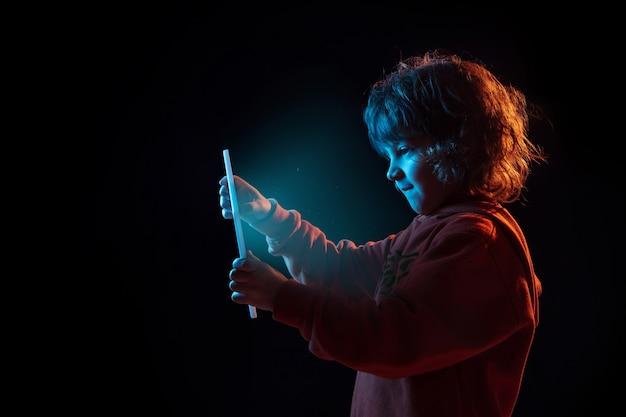 Vlogging con tableta, jugando. retrato de niño caucásico sobre fondo oscuro de estudio en luz de neón. preciosa modelo rizada. concepto de emociones humanas, expresión facial, ventas, publicidad, tecnología moderna, gadgets.