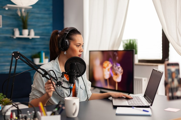 Vloguera creativa que conversa en línea con su audiencia para un nuevo concepto de vlog. grabación de contenido de redes sociales con auriculares de producción, estación de transmisión de internet web digital