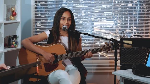 Vocalista de mujer negra grabando una canción y tocando la guitarra en el estudio casero