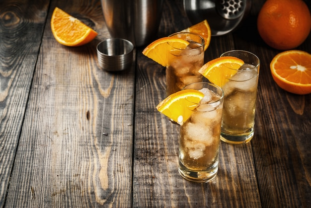Vodka alcohólico whisky orange highball cocktail con una guarnición de naranja en mesa de madera