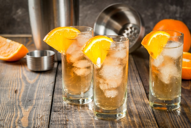 Vodka alcohólico whisky orange highball cocktail con una guarnición de naranja, en mesa de madera