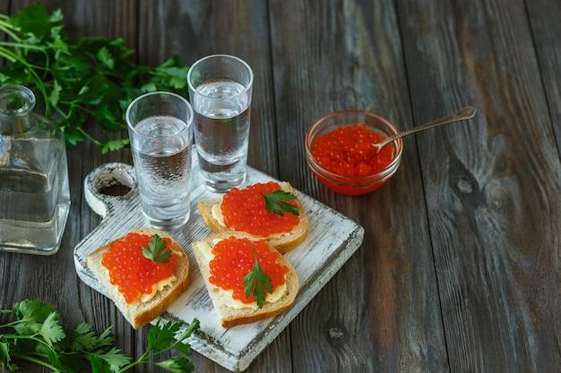 Vodka con caviar de salmón y tostadas de pan sobre mesa de madera
