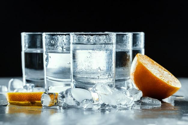 Vodka fría en vasos de medida en un fondo negro.