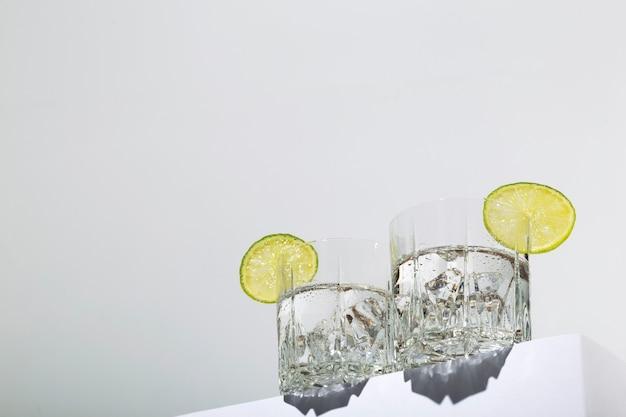 Vodka con hielo y limón en dos vasos sobre soporte blanco. vista de héroe, sombras y tendencias de luz solar.