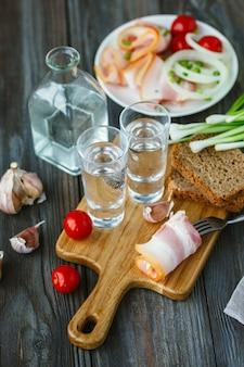 Vodka con manteca de cerdo y cebolla verde en la pared de madera.