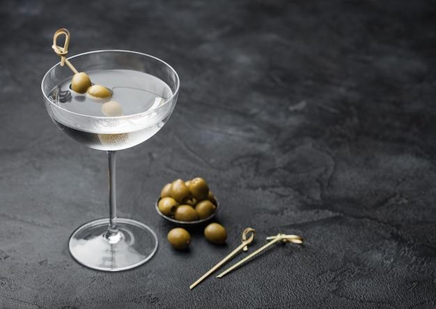 Vodka martini gin cocktail en vaso moderno con aceitunas en recipiente de metal y palos de bambú sobre superficie negra.vista superior