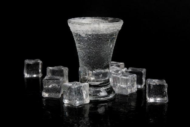 Vodka ruso con hielo sobre una mesa negra