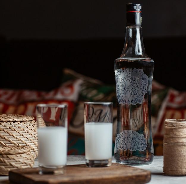 Vodka turco raki en vasos con una botella a un lado.