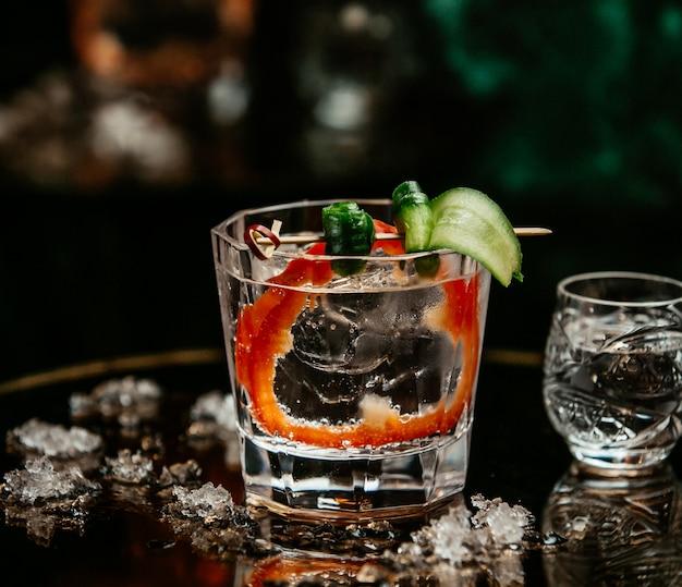 Vodka en vaso con rodaja de olivo, pepino y pimiento rojo.