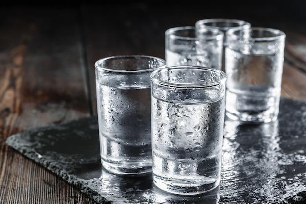Vodka en vasos de chupito en madera rústica