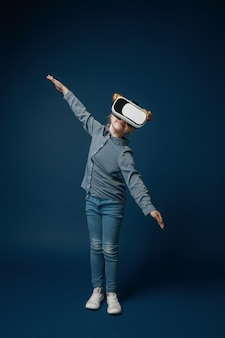 Volando como un avión. niña o niño en jeans y camisa con gafas de casco de realidad virtual aisladas sobre fondo azul de estudio. concepto de tecnología de punta, videojuegos, innovación.