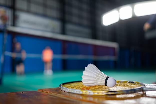 Volante de bádminton y raqueta con desenfoque de fondo de jugador