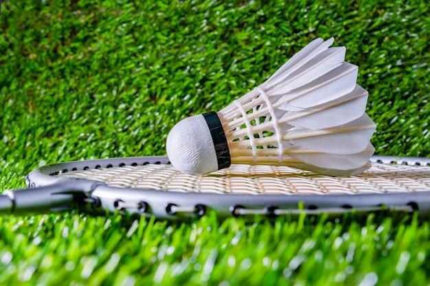 Volante de bádminton sobre hierba con raqueta